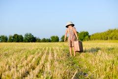 Rapaz pequeno que anda mala de viagem velha grande afastado levando Fotos de Stock Royalty Free
