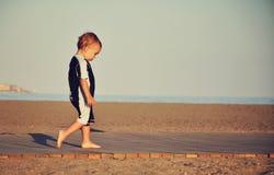 Rapaz pequeno que anda na praia Fotografia de Stock