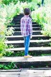 Rapaz pequeno que anda nas escadas que vão subida Imagem de Stock