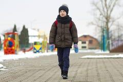 Rapaz pequeno que anda no parque Criança que vai para uma caminhada após a escola com um saco de escola no inverno Atividade das  imagem de stock royalty free