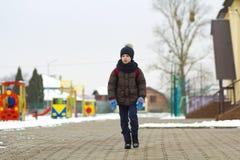 Rapaz pequeno que anda no parque Criança que vai para uma caminhada após a escola com um saco de escola no inverno Atividade das  imagem de stock
