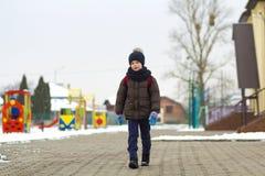 Rapaz pequeno que anda no parque Criança que vai para uma caminhada após a escola com um saco de escola no inverno Atividade das  fotografia de stock