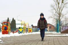 Rapaz pequeno que anda no parque Criança que vai para uma caminhada após o sch fotos de stock royalty free