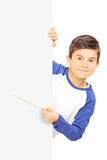 Rapaz pequeno que aponta em um painel vazio com vara Fotos de Stock Royalty Free