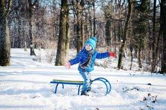 Rapaz pequeno que aprecia um passeio do trenó Sledding da criança foto de stock royalty free
