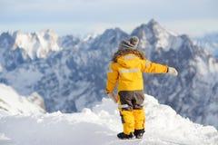 Rapaz pequeno que aprecia a vista das montanhas do cume do inverno fotografia de stock royalty free