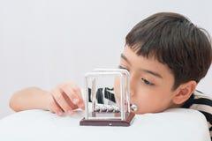 Rapaz pequeno que aprende a bola do equilíbrio do newton para o physic da ciência fotografia de stock
