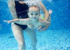 Rapaz pequeno que aprende nadar em uma piscina Fotos de Stock Royalty Free