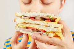 Rapaz pequeno que aspira o sanduíche saboroso no fim branco do fundo acima fotografia de stock