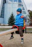 Rapaz pequeno que balança no balanço no campo de jogos Fotografia de Stock Royalty Free