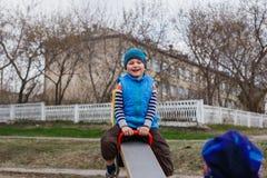 Rapaz pequeno que balança no balanço no campo de jogos na mola Imagem de Stock
