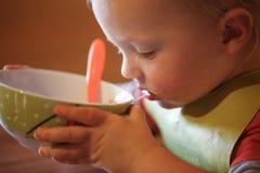 Rapaz pequeno que bebe independentemente de uma bacia fotos de stock