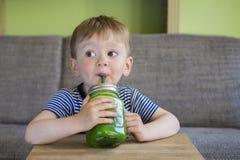 Rapaz pequeno que bebe um batido verde Foto de Stock Royalty Free