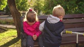 Rapaz pequeno que beija a menina triste em um banco de parque vídeos de arquivo