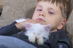Rapaz pequeno que beija um gato macio branco no sofá fotos de stock royalty free
