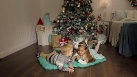 Rapaz pequeno que beija uma menina perto da árvore de Natal filme