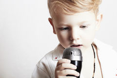 Rapaz pequeno que canta em microphone.child em karaoke.music imagens de stock