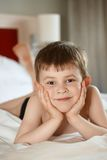Rapaz pequeno que coloca na cama Imagem de Stock