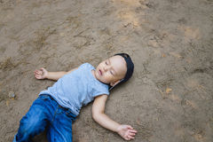 Rapaz pequeno que coloca no sono de fingimento à terra ou inconsciente fotografia de stock