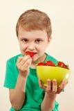 Rapaz pequeno que come morangos doces da bacia Imagem de Stock