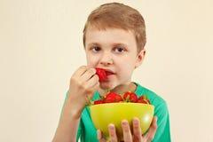 Rapaz pequeno que come morangos doces frescas da bacia Imagem de Stock Royalty Free