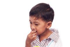 Rapaz pequeno que come o alimento de petisco Foto de Stock Royalty Free