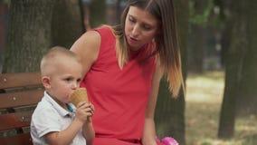Rapaz pequeno que come o gelado em um banco de parque vídeos de arquivo