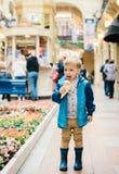 Rapaz pequeno que come o gelado em uma rua Foto de Stock Royalty Free