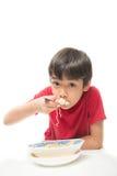 Rapaz pequeno que come o macarronete imediato no fundo branco foto de stock royalty free