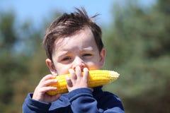 Rapaz pequeno que come o milho fervido fresco foto de stock royalty free