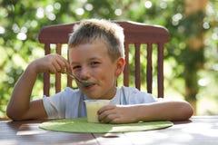 Rapaz pequeno que come o pudim foto de stock