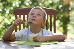 Rapaz pequeno que come o pudim imagem de stock