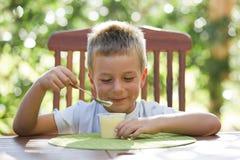 Rapaz pequeno que come o pudim Imagens de Stock