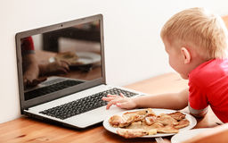 Rapaz pequeno que come a refeição ao usar o laptop em casa Imagens de Stock
