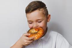 Rapaz pequeno que come um bagel com sementes de papoila Fotografia de Stock