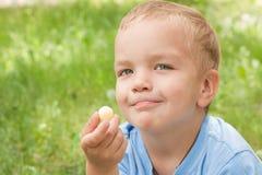 Rapaz pequeno que come um petisco. Fotografia de Stock