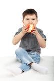 Rapaz pequeno que come uma maçã vermelha Fotografia de Stock Royalty Free