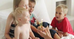 Rapaz pequeno que comemora seu aniversário com um bolo e os amigos filme