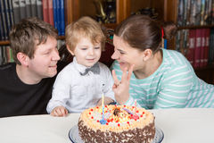 Rapaz pequeno que comemora seu aniversário em casa com seus pais foto de stock royalty free