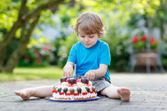 Rapaz pequeno que comemora seu aniversário no jardim da casa com Ca grande Imagens de Stock Royalty Free