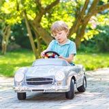 Rapaz pequeno que conduz o carro velho do brinquedo grande, fora Imagens de Stock