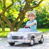 Rapaz pequeno que conduz o carro velho do brinquedo grande, fora Fotos de Stock Royalty Free