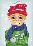 Rapaz pequeno que congela-se no frio do inverno que veste o chapéu e o revestimento de lã com lenço Imagens de Stock