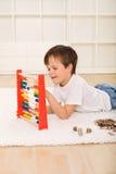 Rapaz pequeno que conta suas economias Imagens de Stock