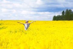 Rapaz pequeno que corre em um campo de flores amarelas Fotografia de Stock Royalty Free