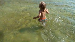 Rapaz pequeno que corre na água video estoque
