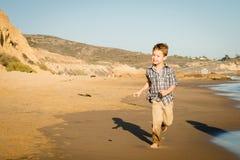 Rapaz pequeno que corre na praia Imagem de Stock