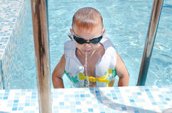 Rapaz pequeno que cospe para fora um bocado da água Foto de Stock