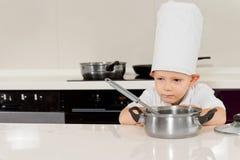 Rapaz pequeno que cozinha a dobra para baixo para cheirar o alimento imagem de stock royalty free