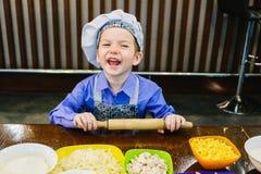 Rapaz pequeno que cozinha a pizza imagem de stock royalty free
